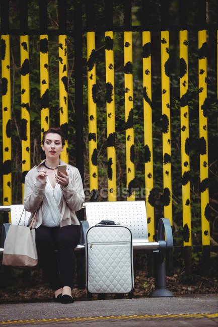 Junge Frau sitzt auf Bank am Bahnsteig — Stockfoto