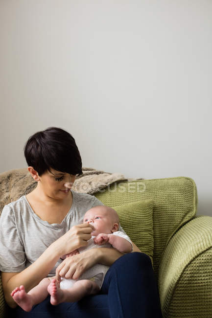 Mother feeding her baby in living room at home — Stock Photo