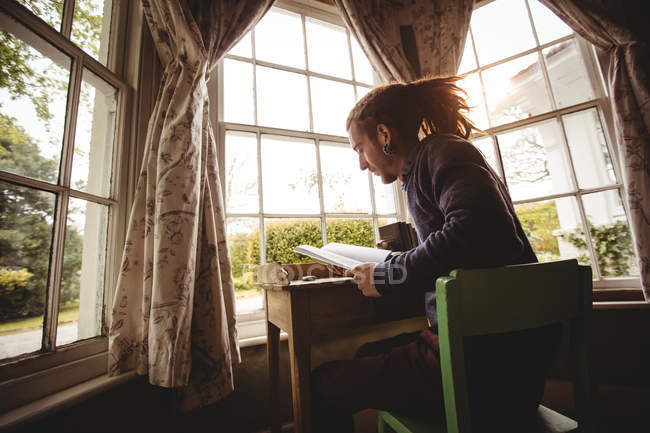 Side view of young man reading book by window at home — Stock Photo