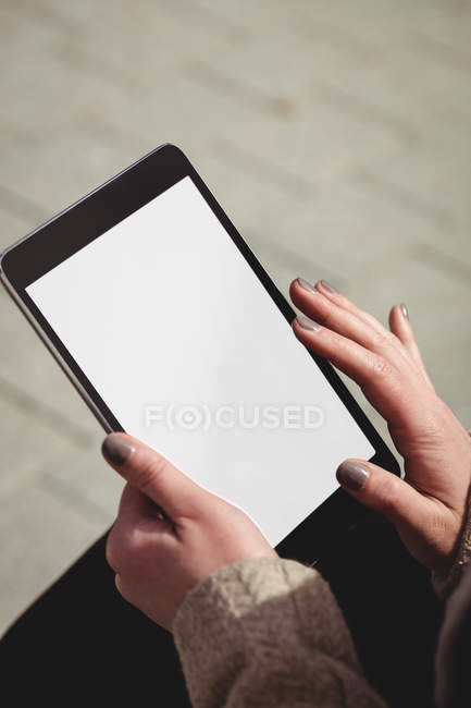 Cropped image of woman using digital tablet on footpath — Stock Photo