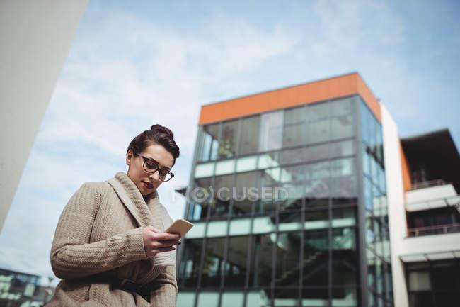 Mujer joven usando el teléfono móvil mediante la construcción - foto de stock
