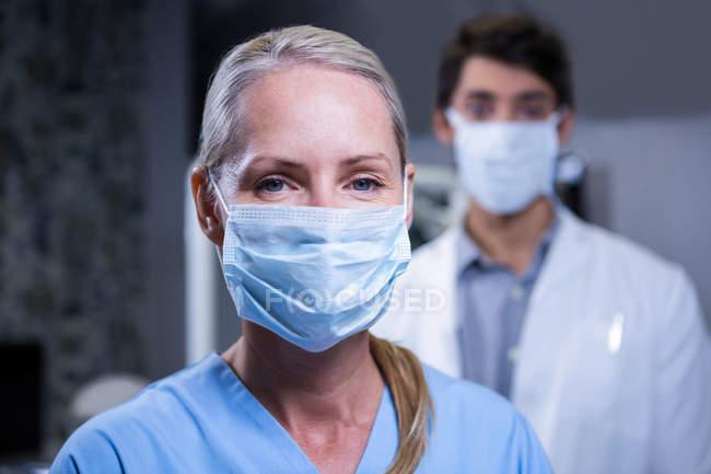 Retrato de assistente odontológico e dentista usando máscaras cirúrgicas na clínica odontológica — Fotografia de Stock