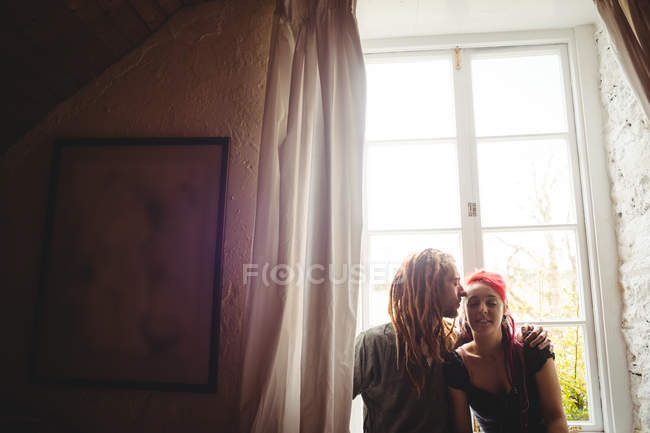 Young hipster couple embracing against window at home — Fotografia de Stock