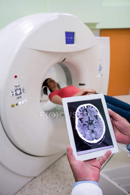 Médico mirando la resonancia magnética cerebral en la tableta digital en el hospital - foto de stock