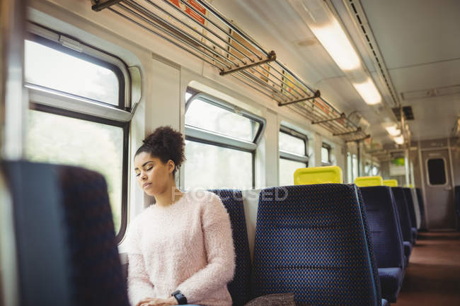 Young woman napping while sitting in train — Stock Photo