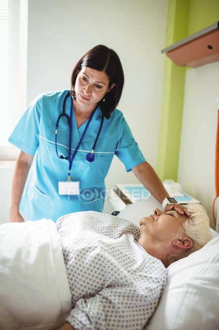 Nurse checking senior patient in hospital — Stock Photo