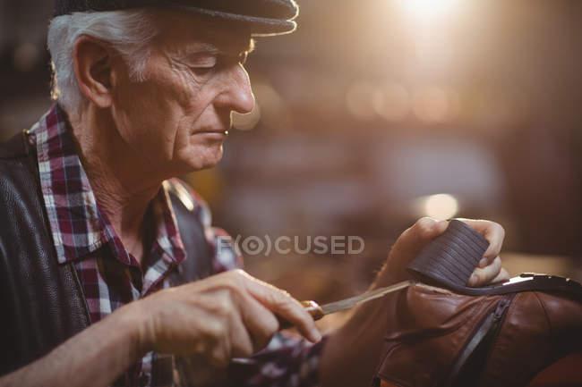 Sapateiro reparando um sapato na oficina — Fotografia de Stock