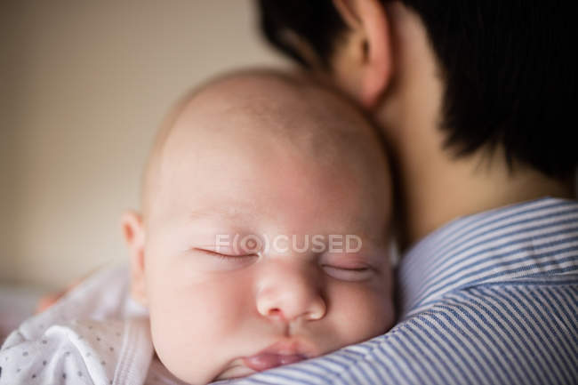 Primer plano del bebé durmiendo en el hombro de la madre en casa - foto de stock
