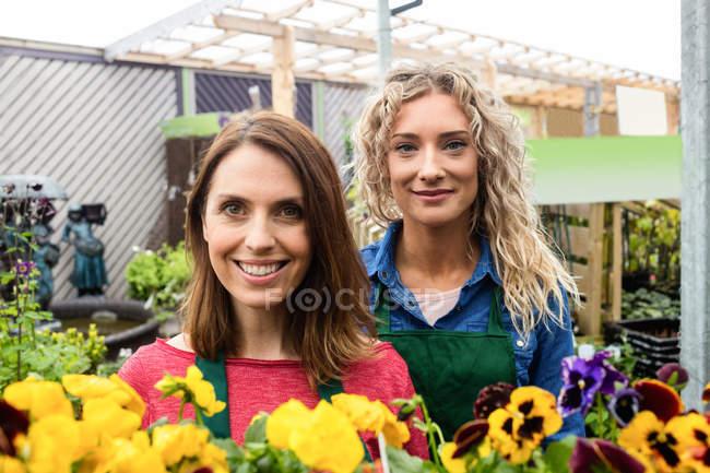 Портрет двух женских флористов, улыбаясь в садовом центре — стоковое фото