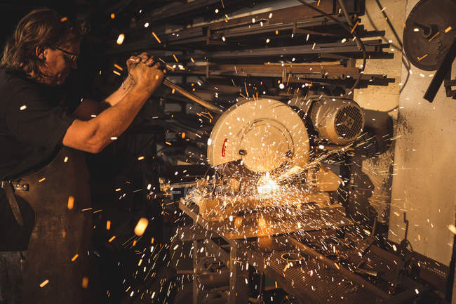 Blacksmith using circular saw machine in workshop — Stock Photo