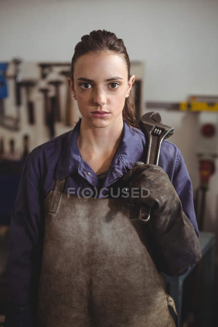 Female welder holding wrench tool in workshop — Stock Photo