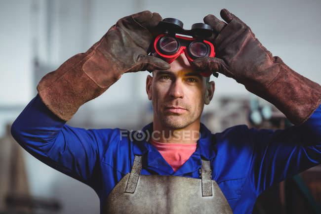 Masculin soudeur tenant des lunettes de soudage en atelier — Photo de stock