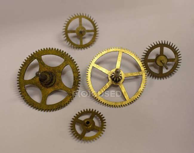 Collection of five clock gears on white paper in workshop — Stock Photo