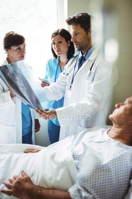 Врачи, взаимодействующих через рентген отчет с пациентом в стационаре — стоковое фото