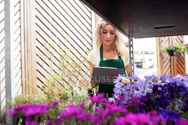 Писательница-флористка на планшете в центре сада — стоковое фото