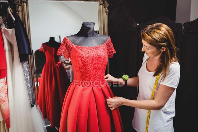 Creative designer adjusting dress on mannequin — Stock Photo