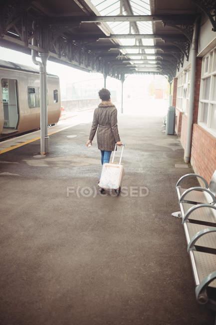 Vue arrière de la femme portant des bagages en marchant sur le quai de la gare — Photo de stock
