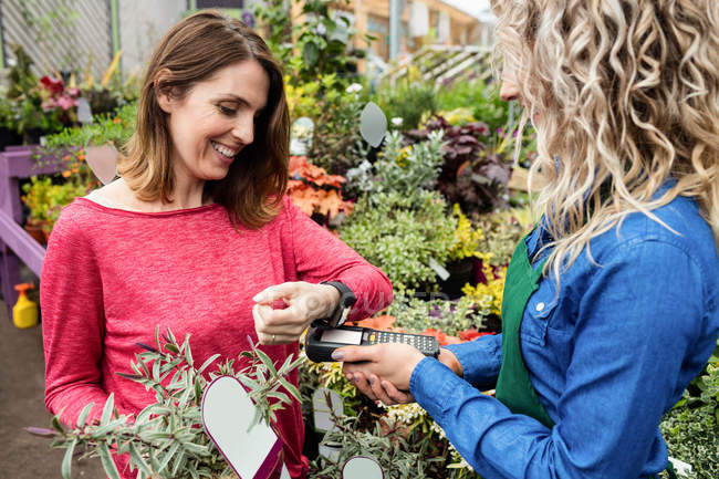 Woman making payment through smart watch in garden centre — Stock Photo
