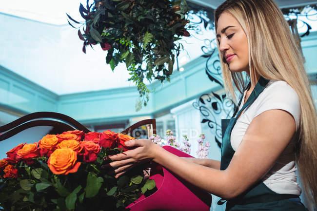 Florista feminina derramando água em vaso de flores em sua loja de flores — Fotografia de Stock
