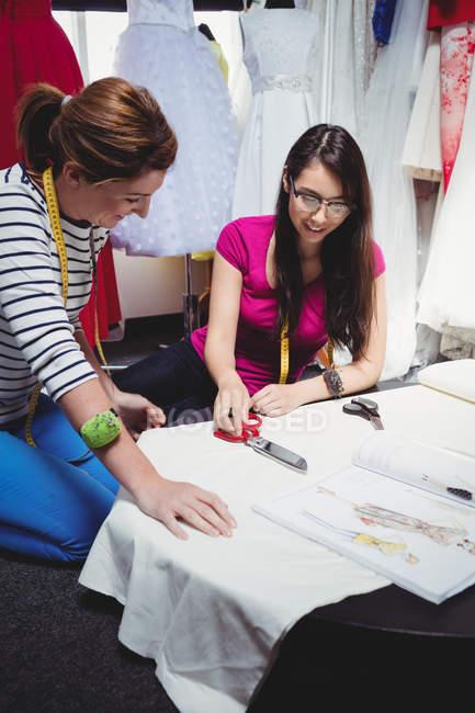 Créatrices de mode travaillant sur ordinateur portable en studio — Photo de stock