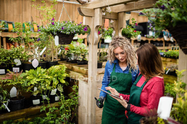Two female florists using digital tablet at garden centre — Stock Photo
