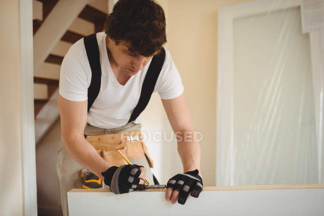 Carpenter measuring wooden door with pencil at home — Stock Photo
