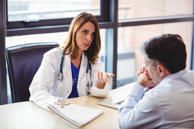 Arzt am Schreibtisch im Gespräch mit Patient im Krankenhaus — Stockfoto
