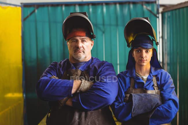 Porträt eines Schweißers und einer Schweißerin, die mit verschränkten Armen in der Werkstatt stehen — Stockfoto