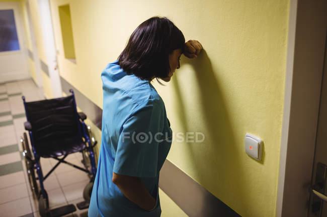 Депрессии медсестра, стоя в коридоре больницы — стоковое фото
