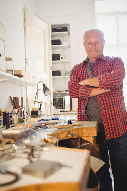 Portrait of goldsmith standing with arms crossed in workshop — Stock Photo
