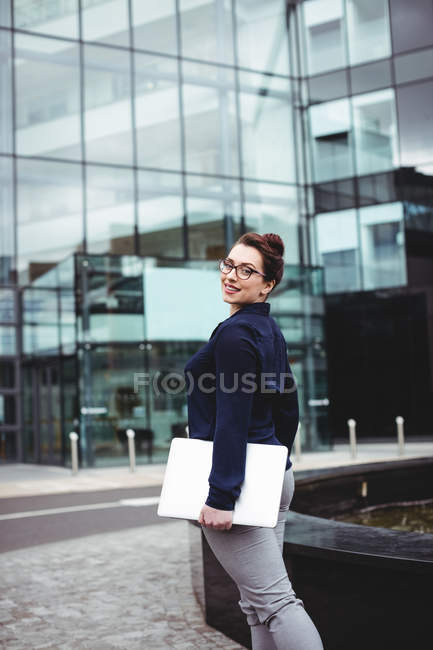 Portrait of smiling businesswoman with laptop outside office building — Stock Photo