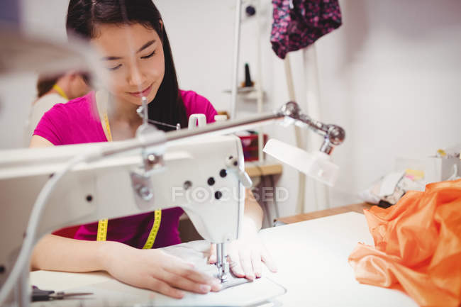 Female dressmakers sewing on sewing machines in studio — Stock Photo