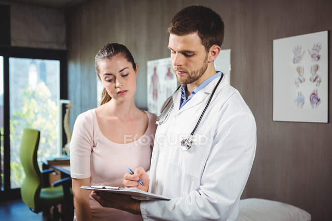 Fisioterapeuta explicando diagnóstico para paciente do sexo feminino na clínica — Fotografia de Stock