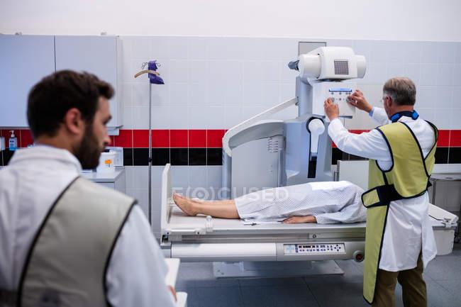 Лікарі, за допомогою рентгенівський апарат для вивчення пацієнта у лікарні — стокове фото