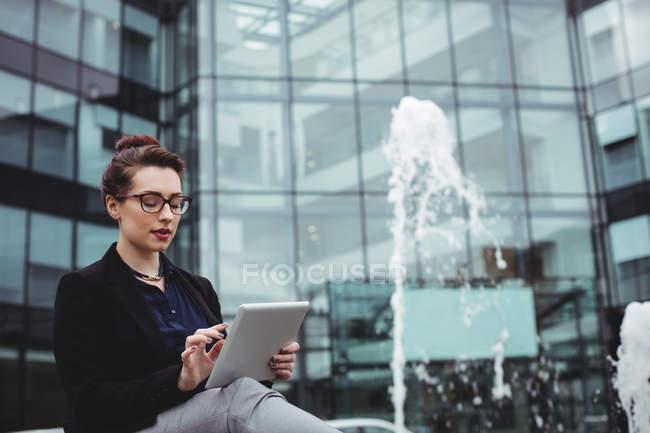 Donna d'affari che utilizza tablet digitale da fontana fuori edificio per uffici — Foto stock