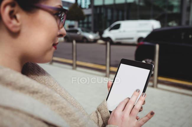 Жінка, використовуючи цифровий планшет на тротуарі — стокове фото