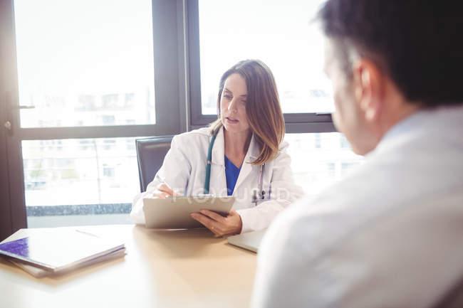 Médecin assis au bureau, écrivant sur le presse-papiers devant le patient à l'hôpital — Photo de stock