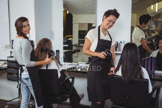 Les femmes se font sécher les cheveux avec sèche-cheveux au salon de coiffure — Photo de stock