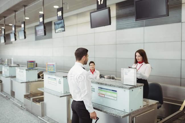 Línea aérea registro asistentes revisar el pasaporte del pasajero en el mostrador de facturación de aeropuerto - foto de stock