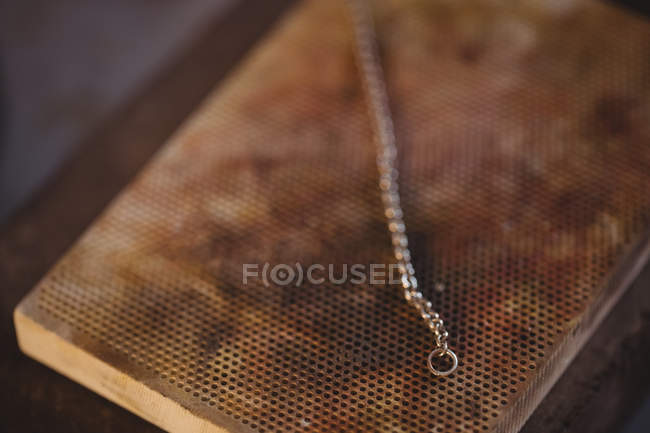 Chain kept on heated bar in workshop — Stock Photo