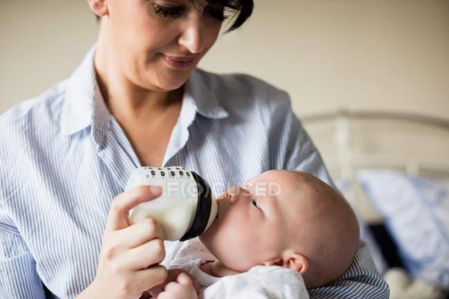 Primer plano del bebé lactante con biberón en casa - foto de stock