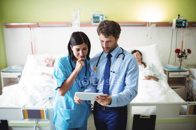 Врач и медсестра с помощью цифрового планшета в палате больницы — стоковое фото