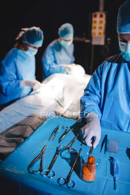 Surgeon taking scissors from tray during operation — Stock Photo
