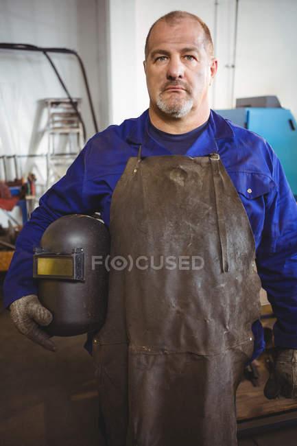 Portrait of welder holding welding helmet in workshop — Stock Photo