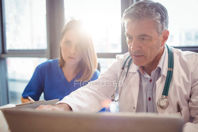 Doctor discussing with nurse over laptop at hospital — Stock Photo