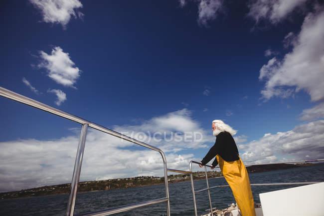 Vue à angle bas du pêcheur regardant la vue du bateau de pêche — Photo de stock