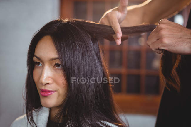 Hairdresser styling customer hair in salon — Stock Photo