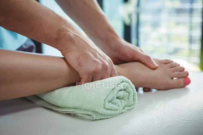 Кадроване зображення фізіотерапевт, даючи фізичної терапії для ніг жінки пацієнта в клініку — стокове фото