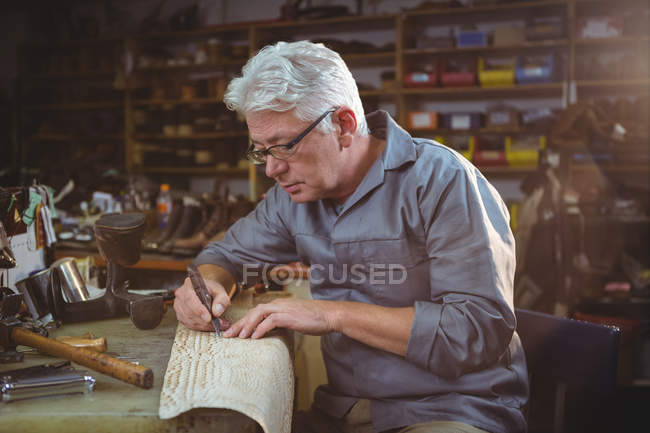 Senior shoemaker cutting a piece of material in workshop — Stock Photo