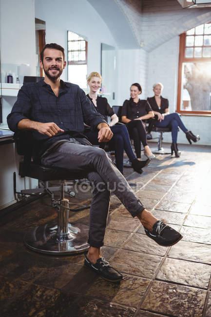 Ritratto di parrucchieri sorridenti seduti su sedie in salone — Foto stock